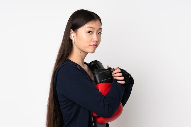 Potomstwa bawją się azjatykciej kobiety na biel ścianie z bokserskimi rękawiczkami