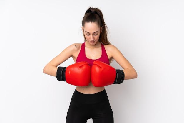 Potomstwa bawją się brunetki kobiety nad odosobnioną biel ścianą z bokserskimi rękawiczkami