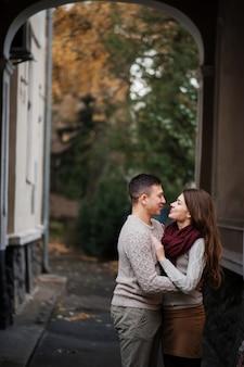 Potomstwa dobierają się być ubranym na wiązanych ciepłych pulowerach ściska w miłości pod łukiem przy miastem w jesieni.