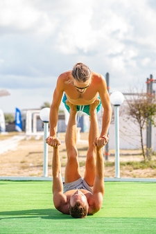 Potomstwa dobierają się kobiety i mężczyzna na polu robi sprawności fizycznej joga ćwiczą wpólnie. element acroyoga zapewniający siłę i równowagę