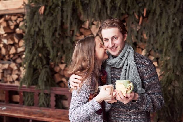 Potomstwa dobierają się mieć śniadanie w romantycznej kabinie outdoors w zimie. ferie zimowe i wakacje. bożenarodzeniowa para szczęśliwy mężczyzna i kobieta pije gorącego wino. para zakochanych