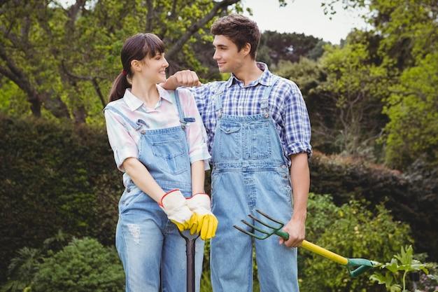 Potomstwa dobierają się mienie łopatę i piking rozwidlenie w ogródzie