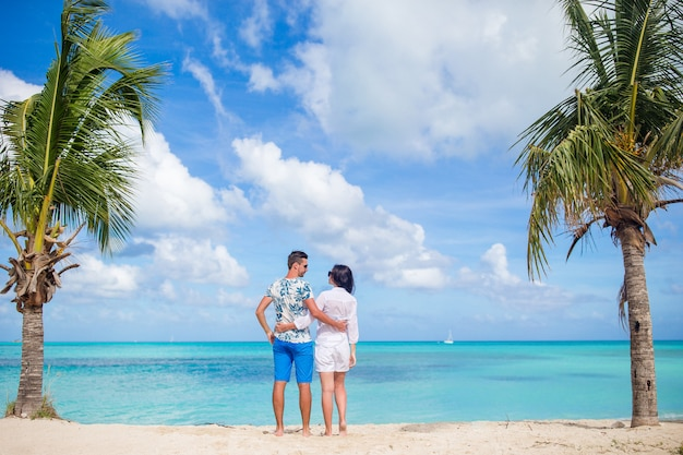 Potomstwa dobierają się na biel plaży, szczęśliwa rodzina na miesiąca miodowego wakacje