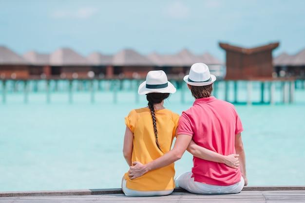 Potomstwa dobierają się na plażowym jetty przy tropikalną wyspą w miesiącu miodowym