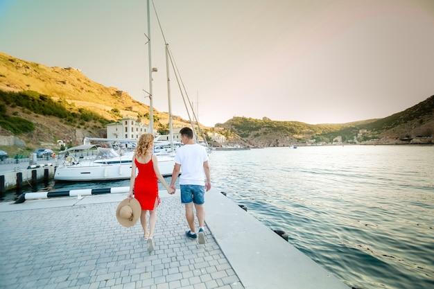 Potomstwa dobierają się uściśnięcia i relaksować przy dokiem blisko łodzi, w pogodnym letnim dniu. kobieta i mężczyzna w modnych ubraniach stoi w pobliżu luksusowego jachtu. luksusowa koncepcja życia. para zakochanych podróżujących, miesiąc miodowy.