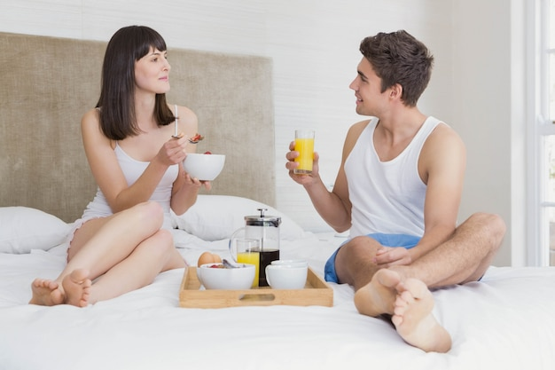 Potomstwa dobierają się uśmiecha się podczas gdy jedzący śniadanie w sypialni wpólnie