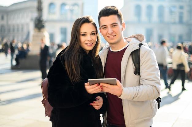 Potomstwa dobierają się używać cyfrową pastylkę plenerową podczas gdy odwiedzający miasto