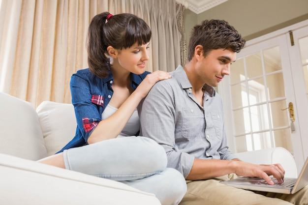 Potomstwa dobierają się używać laptop podczas gdy siedzący na kanapie w żywym pokoju
