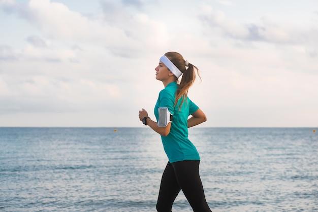 Potomstwa dostosowywali dziewczyna bieg na plaży przy wschodem słońca w ranku