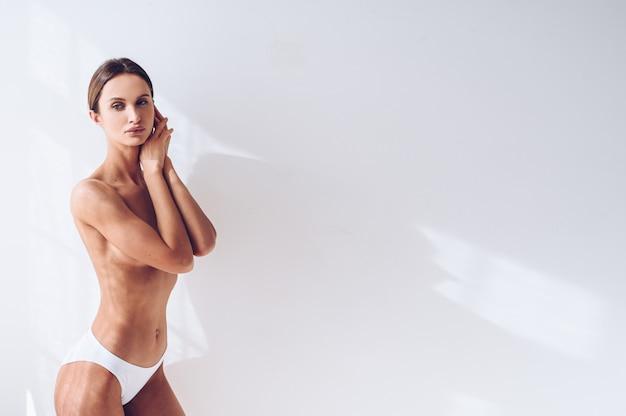 Potomstwa dostosowywali kobiety w białej bieliźnie na biel ścianie odizolowywającej. muskularna szczupła atrakcyjna kobieta z płaskim brzuchem. skopiuj miejsce na tekst. pielęgnacja ciała, zdrowe i sportowe życie, usuwanie włosów, koncepcja jogi