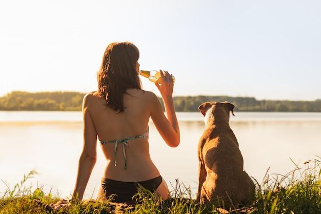 Potomstwa dostosowywali żeńskiego obsiadanie z psem staffordshire teriera na brzeg rzeki i pije butelkę lemoniady lub cidre