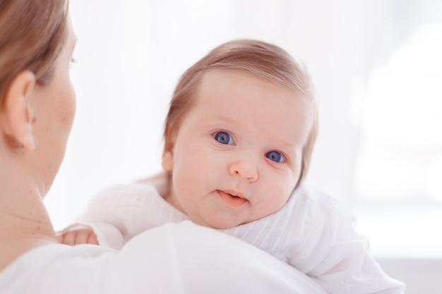 Potomstwa macierzyści i nowonarodzony dziecko w białej sypialni