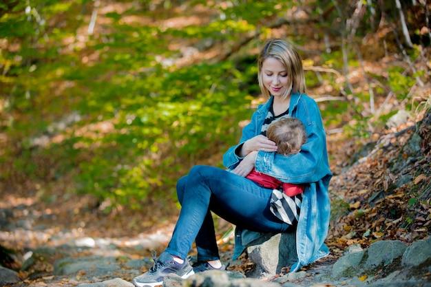 Potomstwa matkują karmić dziecko laktacją w parku.