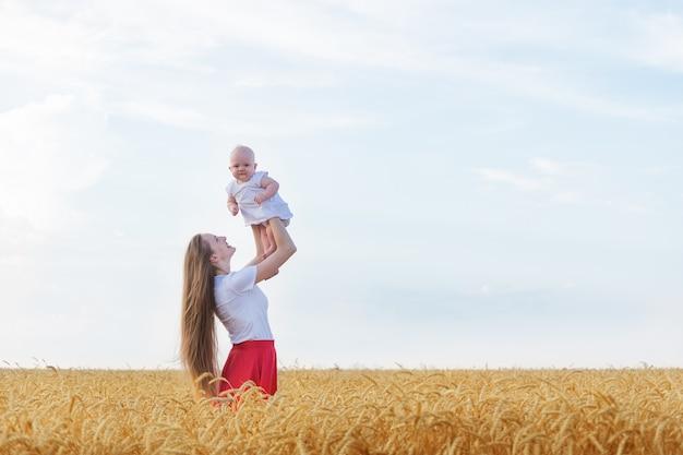 Potomstwa matkują mienia dziecka w jej rękach w pszenicznym polu. wakacje z dziećmi na wsi