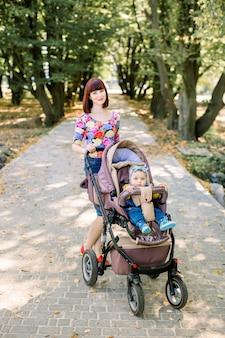 Potomstwa matkują odprowadzenie z uśmiechniętym dzieckiem w brown wózku. rodzice chodzą na zewnątrz z dzieckiem w letnim wózku.