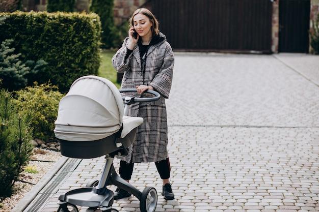 Potomstwa matkują odprowadzenie z wózkiem w parku i rozmawiać przez telefon