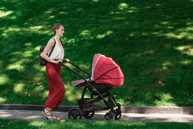 Potomstwa matkują odprowadzenie z wózkiem w parku. spaceruje na świeżym powietrzu z dzieckiem.