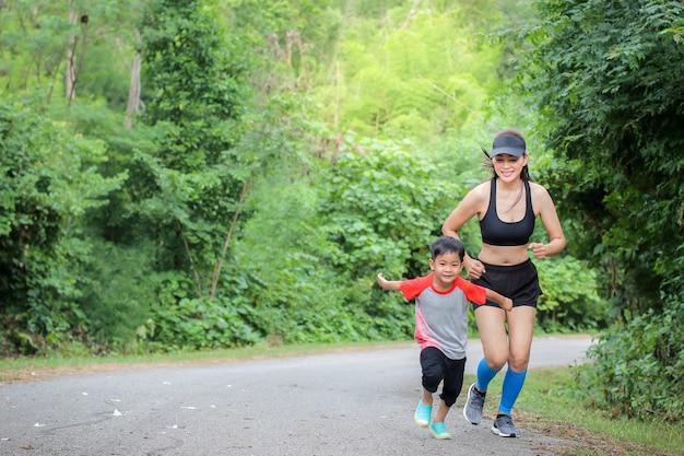 Potomstwa matkują odzież sporta płótno i jej syn chłopiec bieg przy naturą plenerową