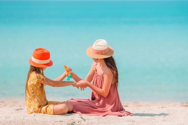 Potomstwa Matkują Stosować Słońce Krem Do Córka Nos Na Plaży. Ochrona Przed Słońcem Premium Zdjęcia