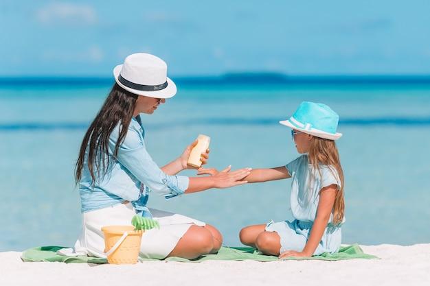 Potomstwa matkują stosować słońce śmietankę córka na plaży.