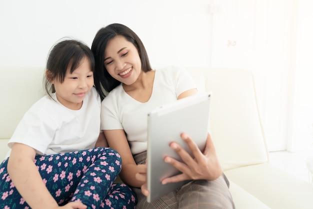 Potomstwa matkują z dziećmi używa cyfrową pastylkę wpólnie w domu. uśmiechnięta rodzina patrzy na ekran, robi zakupy zabawkom lub ogląda kreskówkę online,
