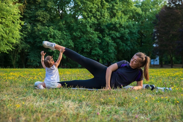 Potomstwa matkują z jej dzieckiem robi ćwiczeniom w parku