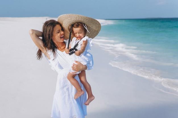 Potomstwa matkują z jej małą córką przy plażą oceanem