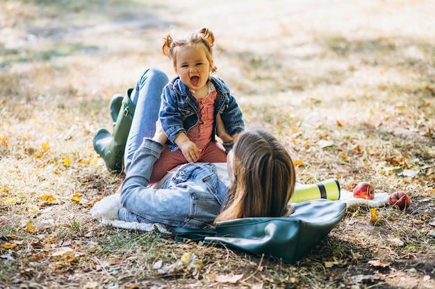 Potomstwa matkują z jej małą córką w jesień parku ma pinkin