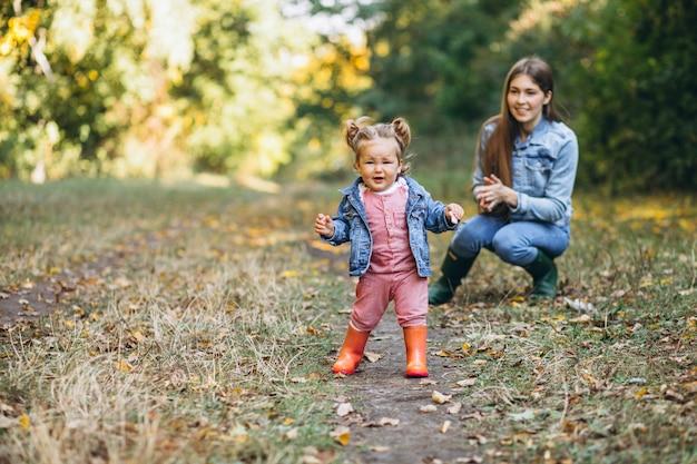 Potomstwa matkują z jej małą córką w jesień parku