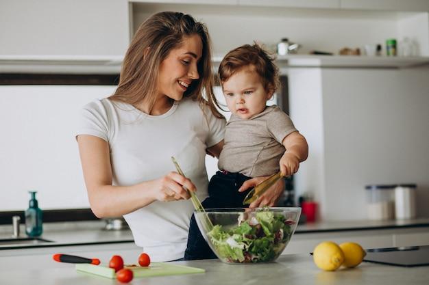 Potomstwa matkują z jej małym synem robi sałatki przy kuchnią