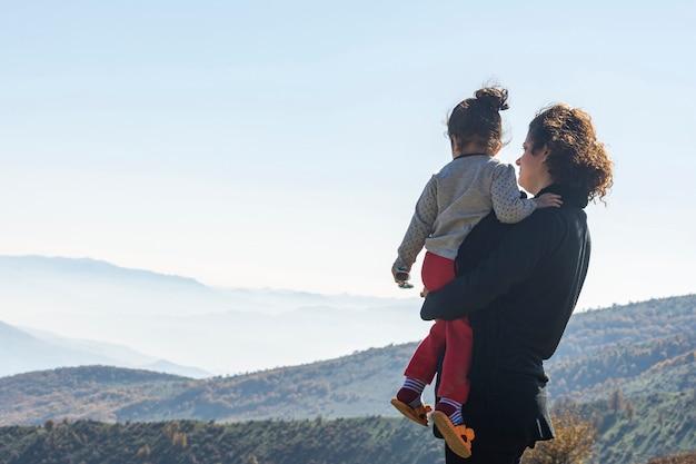 Potomstwa matkują z małą córką patrzeje góry na wakacje