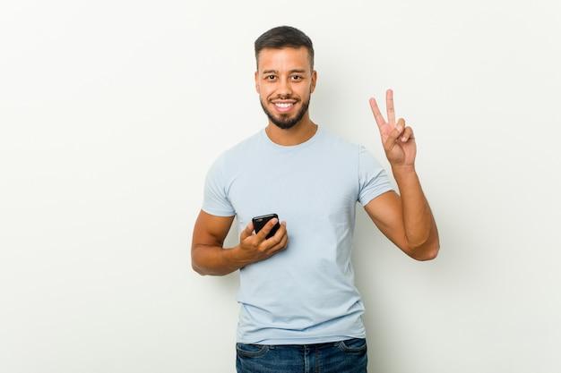 Potomstwa mieszający biegowy azjatykci mężczyzna trzyma telefon pokazuje numer dwa z palcami.
