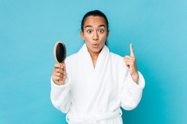Potomstwa mieszający biegowy indianin trzyma hairbrush ma niektóre doskonałego pomysł, pojęcie twórczość.