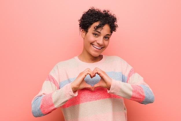 Potomstwa mieszali amerykanina afrykańskiego pochodzenia nastolatka kobiety uśmiecha się kierowego kształt z rękami i pokazuje.