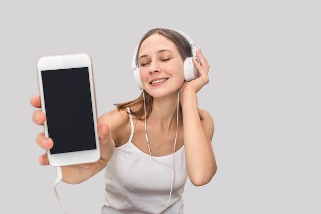 Potomstwa modelują słuchanie muzyka przez białych hełmofonów. ona ma zamknięte oczy i lubi słuchać muzyki. młoda kobieta pokazuje białego telefon w aparacie. na szarym tle.