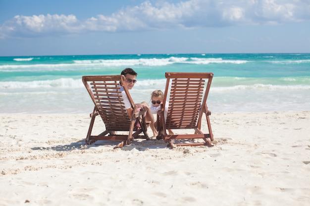 Potomstwa ojcują i jego cudowny córki obsiadanie na plażowych drewnianych krzesłach patrzeje kamerę