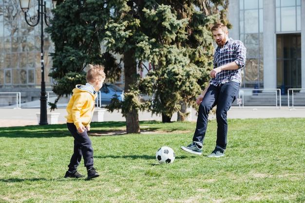 Potomstwa ojcują i jego syn bawić się piłkę nożną w parku