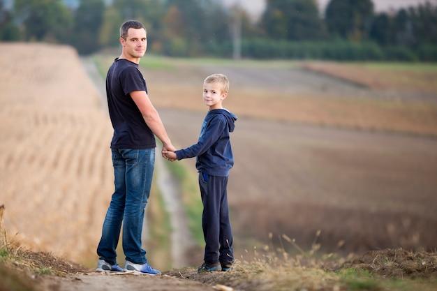 Potomstwa ojcują i uśmiechnięta śliczna dziecko chłopiec pozycja w trawiastego pola mienia rękach