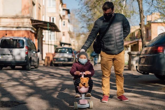 Potomstwa ojcują z dzieckiem na hulajnoga chodzącym outside w medycznych maskach.