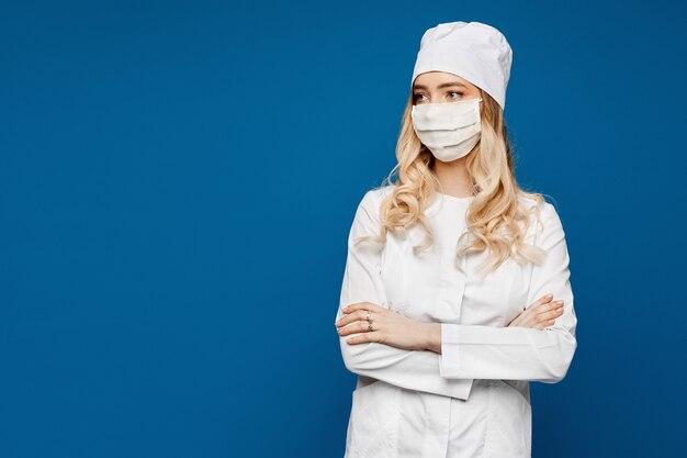 Potomstwa pielęgnują w białej medycznej todze i medycznej masce na błękicie, odizolowywającym. kobiety lekarka w medycznym mundurze i twarzy masce. lekarz ogólny lub stażysta w białym mundurze, służba zdrowia.
