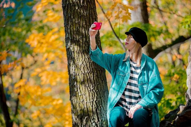 Potomstwa projektują dziewczyny robi selfie z telefonem komórkowym w parku