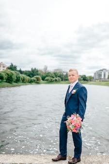 Potomstwa przygotowywają z bukietem kwiaty w jego ręki pozować plenerowy z jeziorem na tle