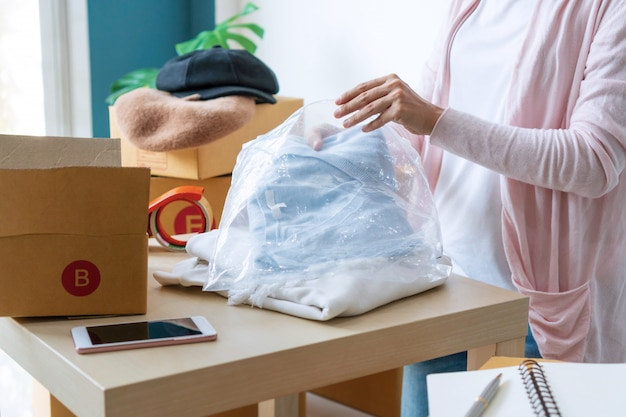 Potomstwa rozpoczynają działalność właściciela firmy pakuje kardigan na stole w miejscu pracy
