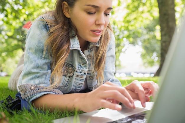 Potomstwa skupiali się studenckiego lying on the beach na trawie używać jej laptop