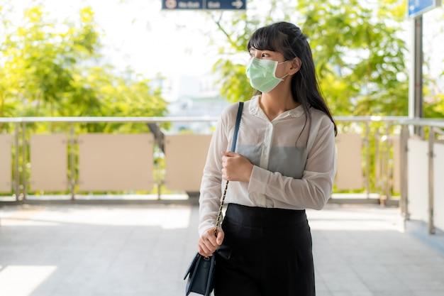 Potomstwa stresują się azjatycki bizneswoman w białej koszula iść pracować w zanieczyszczeniu mieście jest ubranym maskę ochronną zapobiega pyłu pm2.5, smogowi, zanieczyszczeniu powietrza i covid-19 w bangkok, tajlandia.