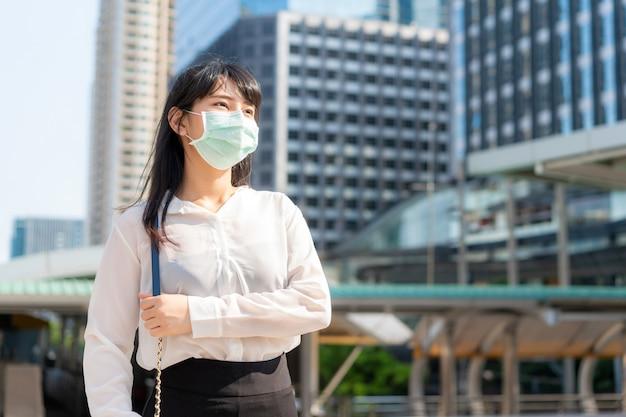 Potomstwa stresują się azjatyckiego bizneswomanu w białej koszula iść pracować w zanieczyszczenia mieście jest ubranym maskę ochronną zapobiega pył i covid-19 z biznesowym budynkiem biurowym w bangkok, tajlandia.