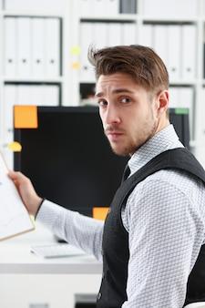 Potomstwa uśmiechają się mężczyzna przy biurowym workspace zbliżeniem