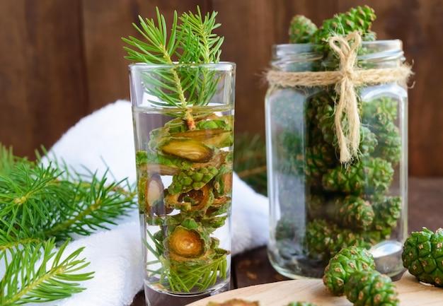 Potomstwa zielenieją jedlinowych rożki na drewnianym stole. do sporządzania naparu leczniczego.
