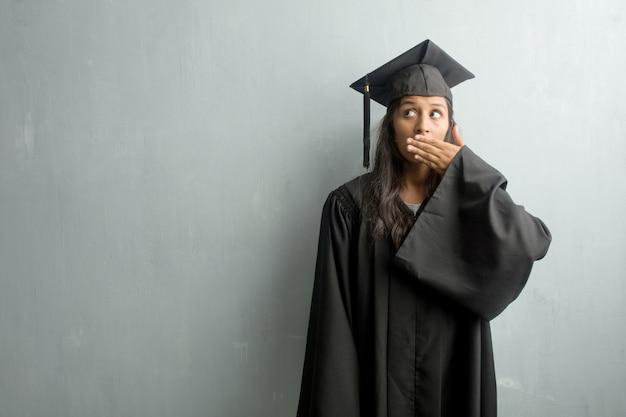 Potomstwo kończąca studia indyjska kobieta przeciw ściennemu nakrywkowemu usta