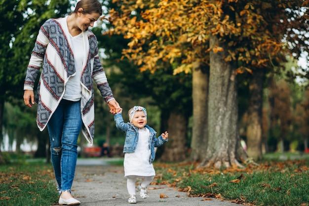 Potomstwo matka z jej małą córką w jesień parku